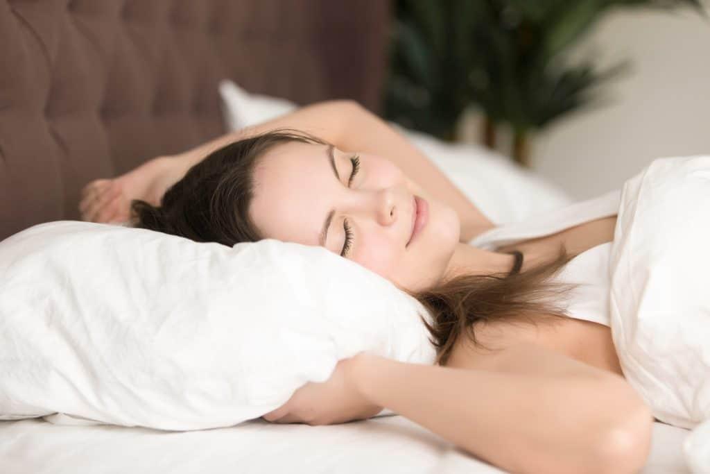 chica bonita sonriendo mientras duerme en cama blanca
