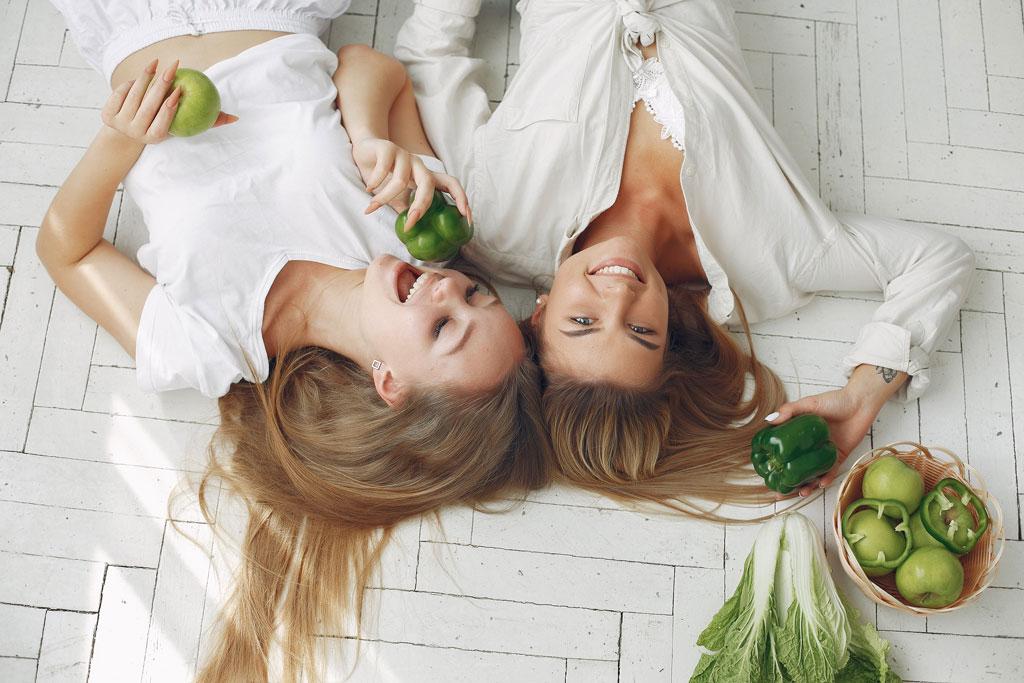 bono-de-4-visitas-de-seguimiento-coaching-nutricional-la-era-de-nuria-chicas-rubias-sonriendo-con-manzanas-verdes