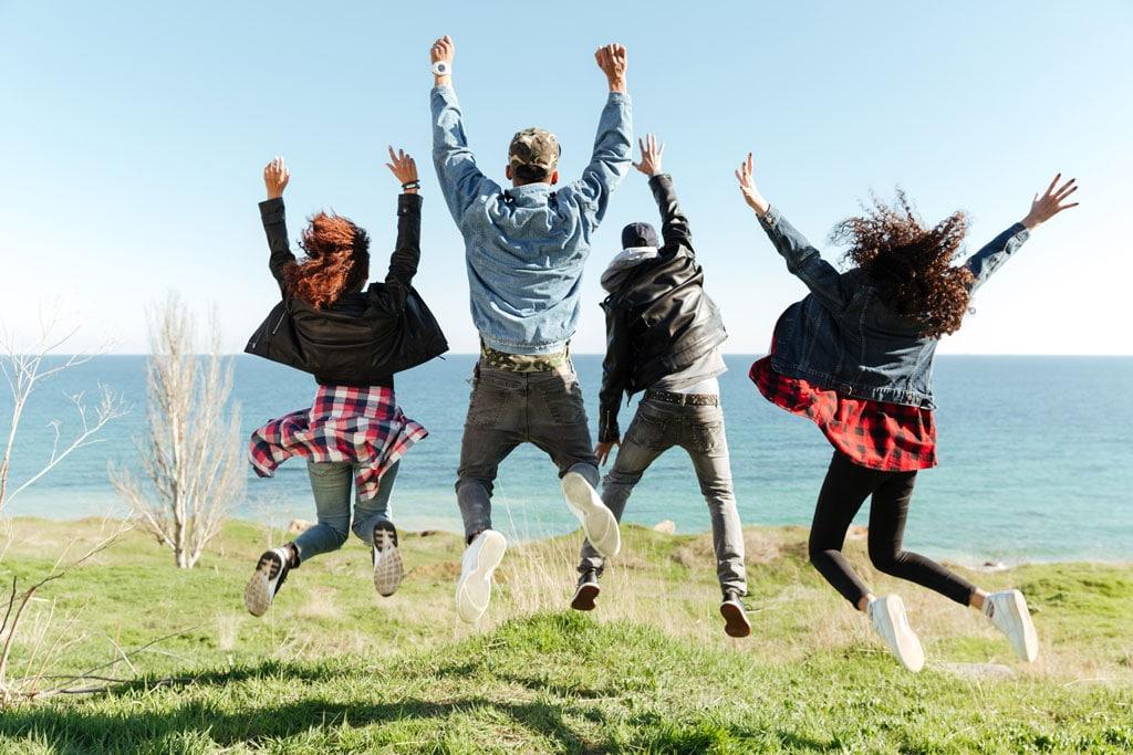 la-era-de-nuria-por-que-grupo de amigos saltando felices de espalda